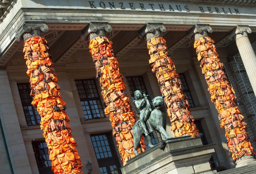Arbeiter befestigen am 13.02.2016 am Konzerthaus in Berlin zahlreiche Rettungswesten. Der chinesische Künstler Ai Weiwei will damit an das Schicksal der vielen Flüchtlinge, die auf ihrem Weg nach Europa ertrunken sind, erinnern. Die Rettungswesten hatte er dazu von der griechischen Insel Lesbos bekommen. Foto: Jörg Carstensen/dpa +++(c) dpa - Bildfunk+++