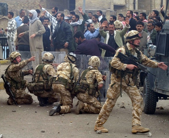 British Army troops take position near a crowd of protesting former Iraqi soldiers after stones were thrown in the southern Iraq city of Basra January 6, 2004. REUTERS/Atef Hassan/File Photo